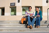 Young couple on steps studying, smiling, portrait, low angle view