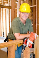 Builder on site in hardhat, smiling, portrait