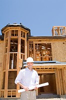 Architect with blueprint in front of partially built house, smiling, portrait, low angle view
