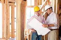 Architect showing blueprint to man in partially built house