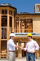 Two businessmen in hardhats shaking hands by partially built house, side view