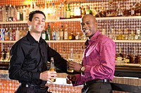 Young man and friend at bar with drinks, smiling, portrait (thumbnail)
