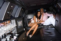 Young couple in limousine, smiling, portrait