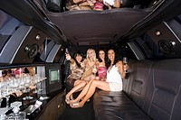 Medium group of young women with drinks in limousine, reflection in ceiling, smiling, portrait