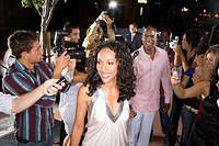Young woman surrounded in paparazzi, smiling (thumbnail)