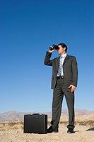 Businessman with briefcase using binoculars in desert, low angle view