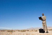 Businessman by briefcase using laptop computer in desert, low angle view (thumbnail)