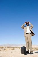 Businessman by briefcase using binoculars in desert, low angle view