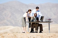 Businessman and woman looking over colleagues shoulders at computer screen on desk in desert