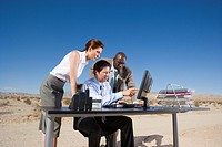 Businessman at desk in desert, showing colleagues work on computer screen