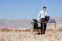 Businessman standing by desk in desert, low angle view