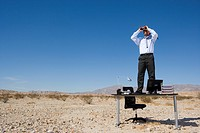 Businessman standing on desk in desert, using binoculars, low angle view