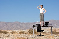 Businesswoman standing on desk in desert, hand on hip, looking into distance