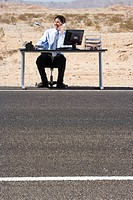 Businessman at desk on side of road in desert, using telephone