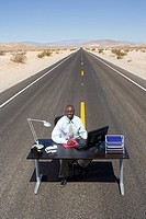 Businessman at desk in middle of road in desert, smiling, portrait, elevated view (thumbnail)