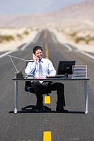 Businessman at desk in middle of road in desert, using telephone
