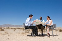 Two businessmen and woman on chairs in desert, looking at map