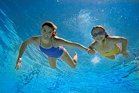 Mother and daughter 8-10 in swimming pool, smiling, portrait, underwater view