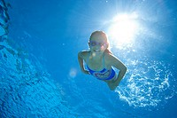 Girl 8-10 in swimming pool, smiling, portrait, underwater view lens flare