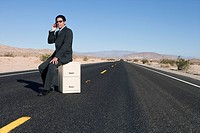 Businessman on filing cabinet in middle of open road in desert, using mobile phone