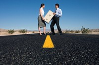 Businessman and woman with filing cabinet on road in desert, low angle view