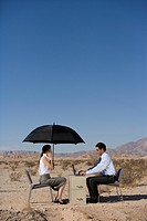 Businessman and woman working in desert, woman with umbrella, side view