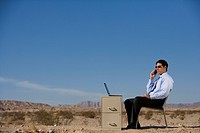 Businessman working in desert, using mobile phone, side view