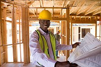 Businessman in hardhat with blueprints in partially built house, smiling, portrait