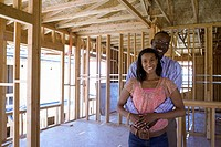 Young couple in partially built house, man embracing woman, smiling, portrait