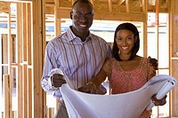 Young couple with blueprints in partially built house, smiling, portrait