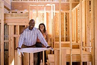 Couple with blueprints in partially built house, smiling, portrait