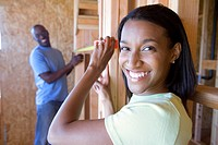 Young couple measuring wall in partially built house, smiling, portrait