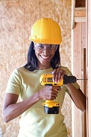 Woman with drill in hardhat in partially built house, smiling, portrait
