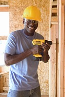 Man with drill in hardhat in partially built house, smiling, portrait