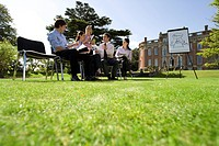 Businessmen and women with folders in training course by manor house, ground view (thumbnail)