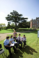 Businessmen and women on chairs on grass by manor house, in training course, elevated view (thumbnail)