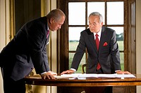 Businessman at desk showing paperwork to colleague