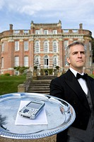 Mature butler with mobile phone on tray by manor house, low angle view (thumbnail)