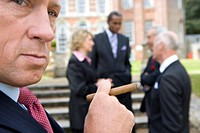 Businessman with cigar by manor house, colleagues in background, close-up