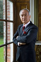 Mature businessman by window, arms crossed, portrait (thumbnail)