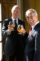 Senior businessman and colleague with drinks, smiling, portrait