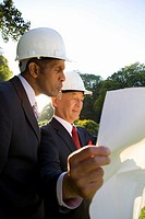 Businessman and colleague in hardhats looking at blueprint, low angle view