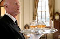 Butler with tray of drinks, low angle view (thumbnail)