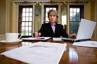Businesswoman with paperwork at table, portrait, low angle view