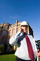 Businessman in hardhat using mobile phone by manor house, low angle view