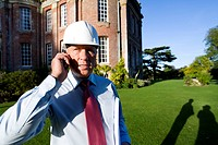 Businessman in hardhat using mobile phone by manor house, portrait