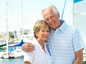 Senior couple arm in arm by boats, smiling, portrait