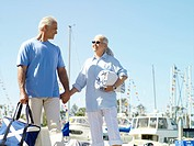 Senior couple hand in hand on jetty, smiling at each other, low angle view
