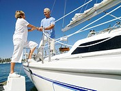 Senior man helping woman onto boat, low angle view