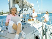 Mature woman using laptop computer on boat, friends in background
